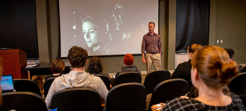 A professor speaks to a group of students sitting in the film viewing room with black and white film on the screen over his shoulder.