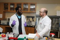 Ben Nkapbela stands in lab with research advisor, Dr. Brian Gray.