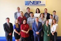 Students stand in front of logo at NATO Support and Procurement Agency.