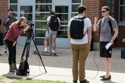 Students gain hands-on experience reporting in the field outside of Wolf Hall.