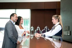 Hospitality management student checks couple in at the hotel front desk.