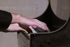 Close up image of hands playing a piano