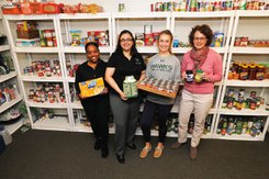 Students and faculty stand holding food in the Spartan Food Pantry.
