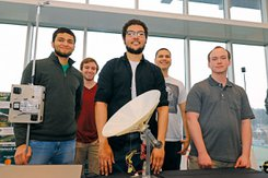 Students who worked on the project stand behind radio telescope mock-up.