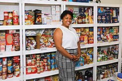 Phillips pictured in front of shelves of food in YCP food pantry