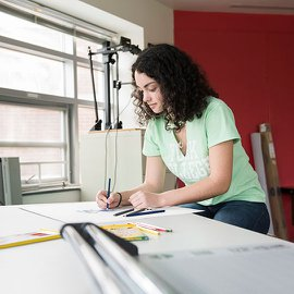 Gevenieve Ryder pictured working on an illustration at a drafting table.