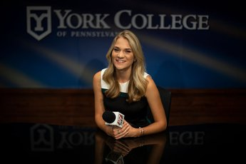 Aimee Lewis sits at news anchor desk with microphone in her hand and York College logo in the background.