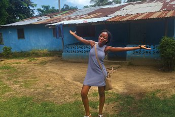 Cathy Cooper '19 stands in front of her childhood home in Liberia.