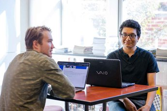 Adrian Castro and Collin Brandt with computers at their internship