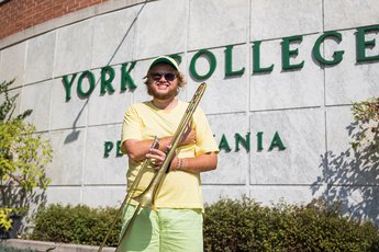 Max Wagaman stands in front of Campbell Hall holding trombone.