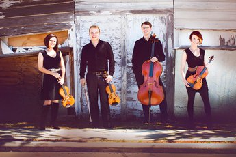 Four members of the Apollo Chamber Players stand with their instruments.