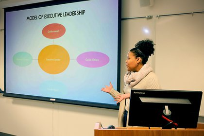 A student gives a presentation in front of her MBA classroom, using a large screen and PowerPoint slides