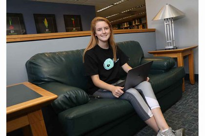Madison sitting on green couch with laptop
