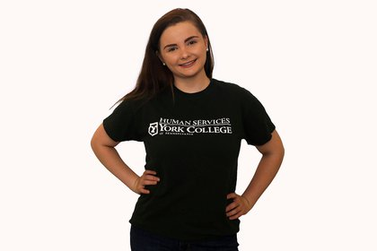 Molly stands wearing a green human services t-shirt.