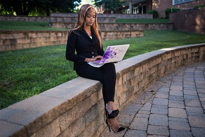 TeAsia wears a suit as she works on her laptop in the campus quad