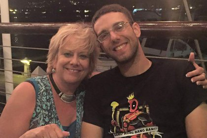 Brandon Shaffer poses with his mother at a table.