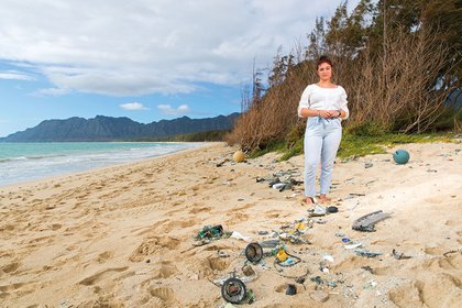 Ana Chew stands on the beach at the shoreline while looking at plastic that washed ashore.