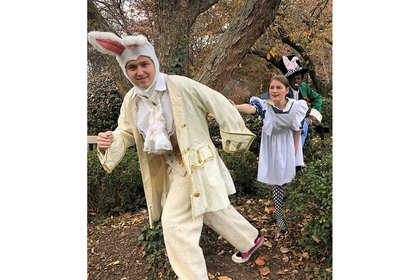 Alice in Wonderland characters sneak through the trees.