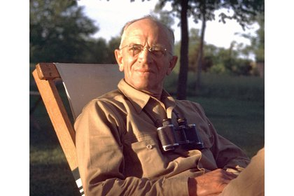 Aldo Leopold sits in chair smiling looking into the sunlight.