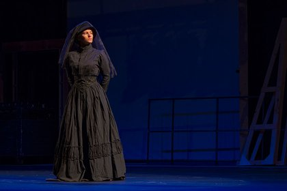 Woman in Black performance of actor on stage.
