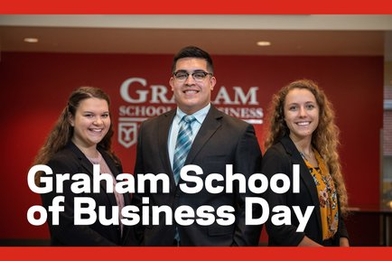 Three students stand in front of a red wall with the Graham School of Business Day text over the image.