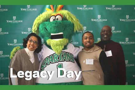 Three people stand with Screamer the mascot with Legacy Day text over the image