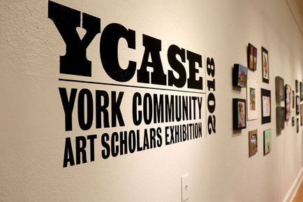 YCASE logo on the wall of the exhibit