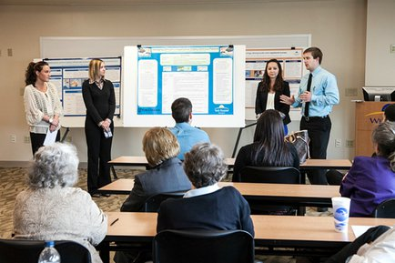 Graham School of Business students present to class on project.