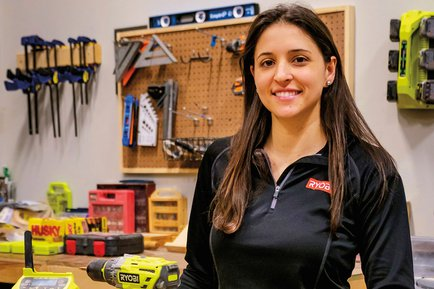 Hannah Krug stands in workshop with Ryobi tools in front of her.