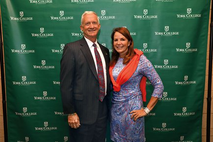 Jeff and Patti Stirk stand in front of York College backdrop for a photo.