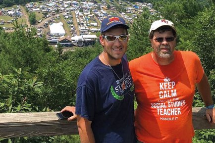 Father and son, Duane and Jacob Swartz stand along the railing of a mountain for a photo.