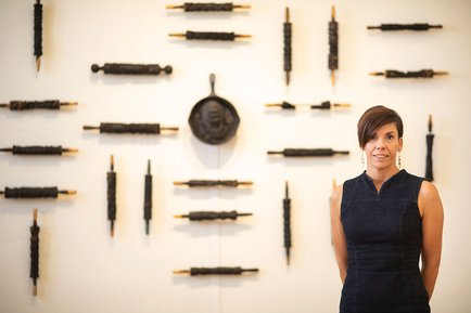 Kelley Gibson stands in front of artwork while posing for a photo.