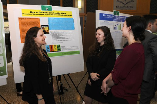 Three female students stand in the Schmidt Library discussing undergraduate research findings.