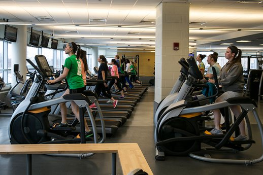 Students exercise on fitness equipment in the fitness center.