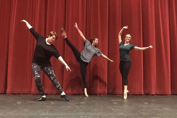 Students dance on stage in front of red curtain in WPAC.