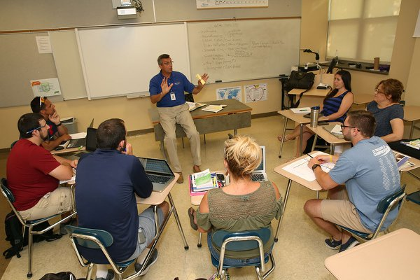 Professor speaks to his students sitting at desks in the classroom.