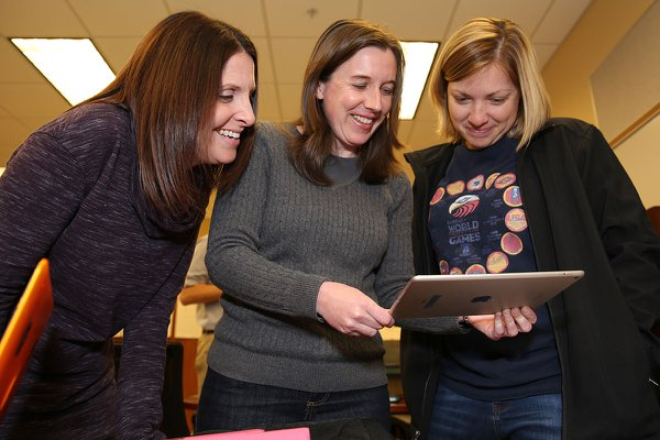 Three female students look at IPad during class.