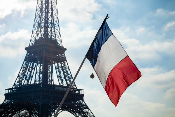 Stock photo of French flag on display in front of the Eiffel Tower.