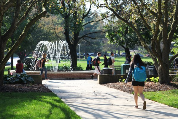 Students walking to class on campus around fountain