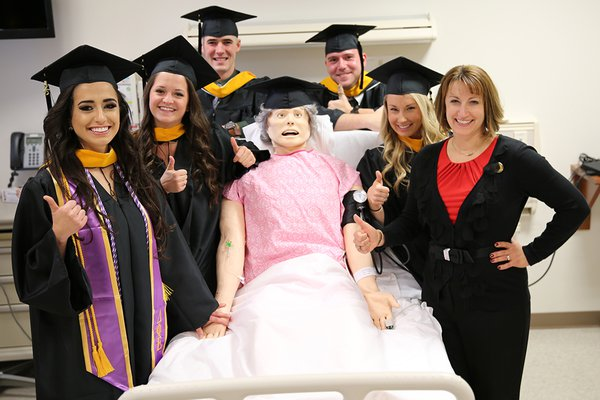 Nursing graduates and a (graduating!) nursing simulator at York College
