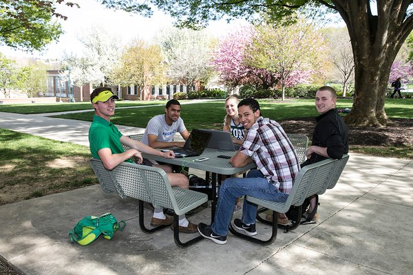 A group of students gathered at a table on main campus.