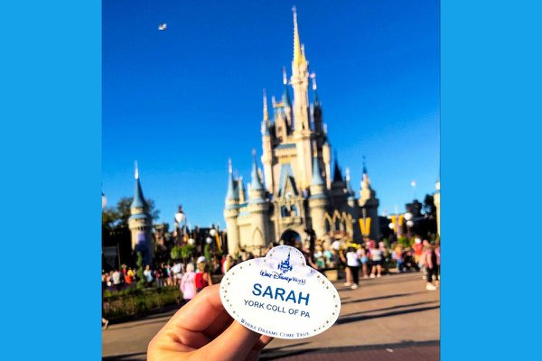 Sarah Rodriguez holds up her Disney name tag in front of Cinderella's Castle