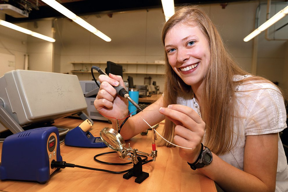 Mikayla Trost smiles at the camera while working on electrical project at a worktable.