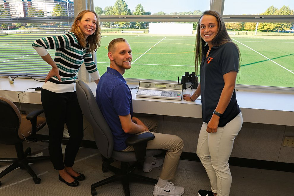 A professor and two students stand in press box overlooking Kinsley Field.