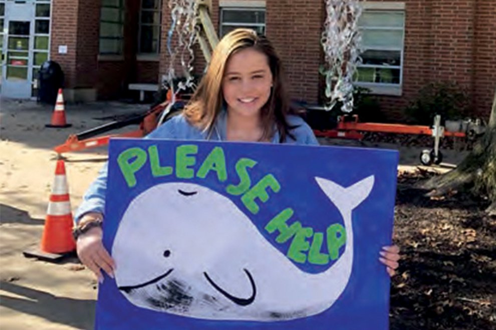 Ashley Ardinger holds a poster with a painted image of a whale and the words Please Help.