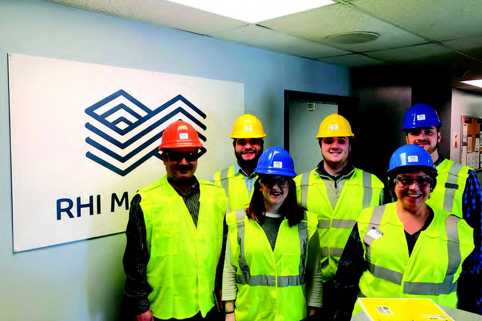 Mary Meisenhelter poses for a group photo with coworkers as they wear construction vests and hardhats