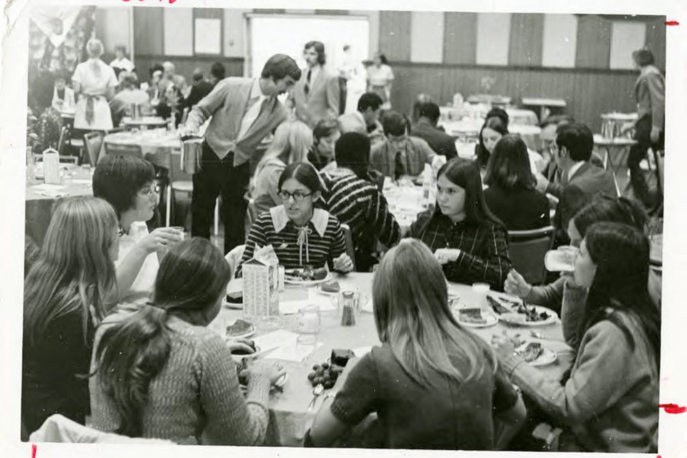 Students gather around round dining tables in an old black and white campus photo
